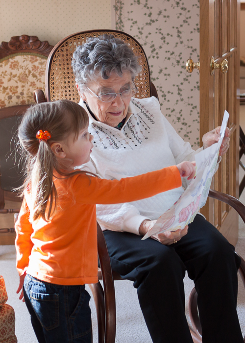 Lily explaining to Great Grandma Amling the artwork she created for her.