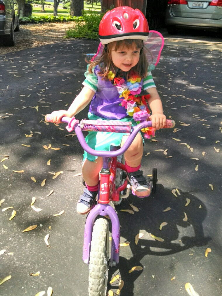 Lily with wings and lei riding her bike.