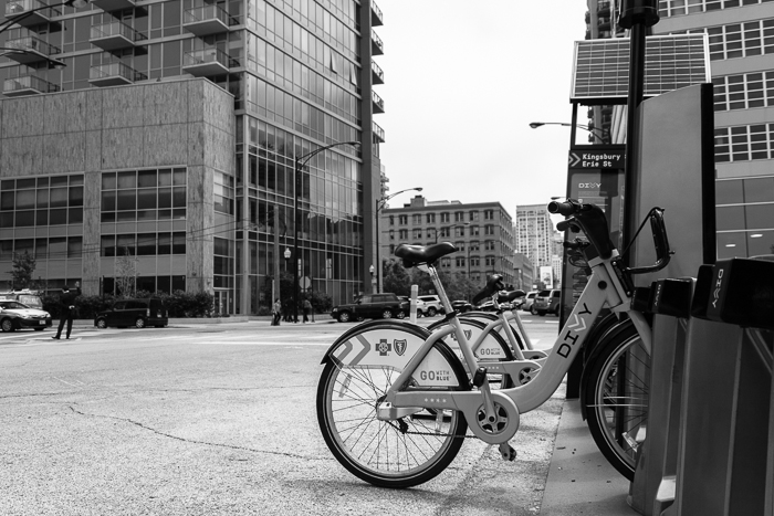 Divvy bikes and a pedestrian flagging down a cab. Near North Side, Chicago.