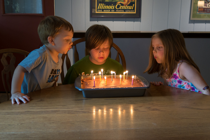 Jamie, Nate, and Lily blowing out birthday candles on Nate's birthday cake.