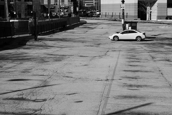 Car sits in an empty, closed off, parking lot. This lot will be part of a new highrise building that begins construction soon. West Loop, Chicago