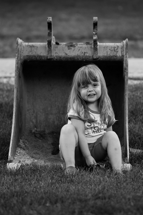 Lily sitting in a excavator bucket left on our lawn from a construction crew working for the township.