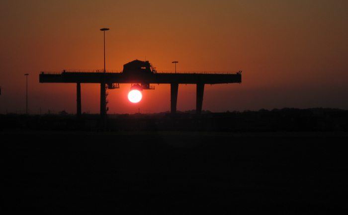 A single container crane appears to be grabbing hold of the sun at sunset in Gardner Kansas at a new BNSF intermodal facility.